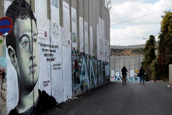 \In this file photo taken on October 15, 2017, two men walk past a new piece of graffiti depicting Facebook founder and CEO Mark Zuckerberg on the controversial Israeli barrier separating the West Bank town of Bethlehem from Jerusalem. Zuckerberg has found himself at the center of a fresh row after saying the social network should not prohibit posts which deny the Holocaust. In a podcast interview with tech website Recode on July 18, 2018, Zuckerberg said that while Facebook was dedicated to stopping the spread of fake news, certain beliefs that were sincerely held would not be taken down. After the remarks caused a backlash on social media, he was forced to backtrack, saying if any post advocated violence or hate against a group, it would be removed.