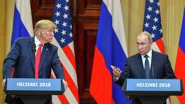 US President Donald Trump, left, listens as Russia's President Vladimir Putin speaks during a joint press conference after a meeting at the Presidential Palace in Helsinki, on Monday. Trump refused to push Putin on Russian interference in U.S. elections.