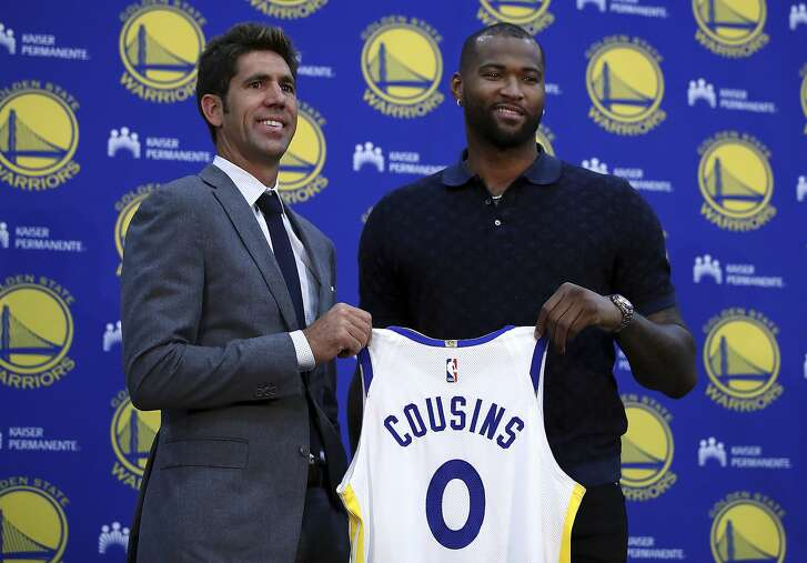 Golden State Warriors General Manager Bob Myers, left, holds a jersey with DeMarcus Cousins during a media conference Thursday, July 19, 2018, in Oakland, Calif. Cousins signed a one-year, $5.3M deal with the defending champion Warriors. (AP Photo/Ben Margot)