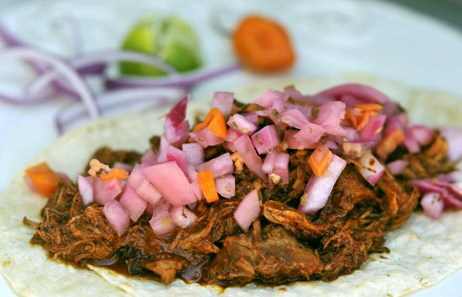 Cochinita pibil Yucatan-style tacos from Chela's Tacos. Photo: Robin Jerstad /Special To The Express-News / Copyright 2011 by Robin Jerstad 210-254-6552