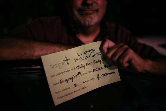 Gregory Louis Smith, 55, shows off his overnight parking permit in the parking lot of the First Presbyterian Church of Hayward in Castro Valley, California, on Wednesday, July 18, 2018. Gregory Louis Smith has been sleeping in his car of the church parking lot.
