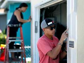 Ryan Baladad strips old paint from the front of a home on Wisteria Drive with Vi Bui (left) in East Palo Alto, Calif. on Thursday, July 19, 2018. Dozens of volunteers came together for Habitat for Humanity's Building Blocks program to make critical repairs for long-time homeowners in underserved neighborhoods.