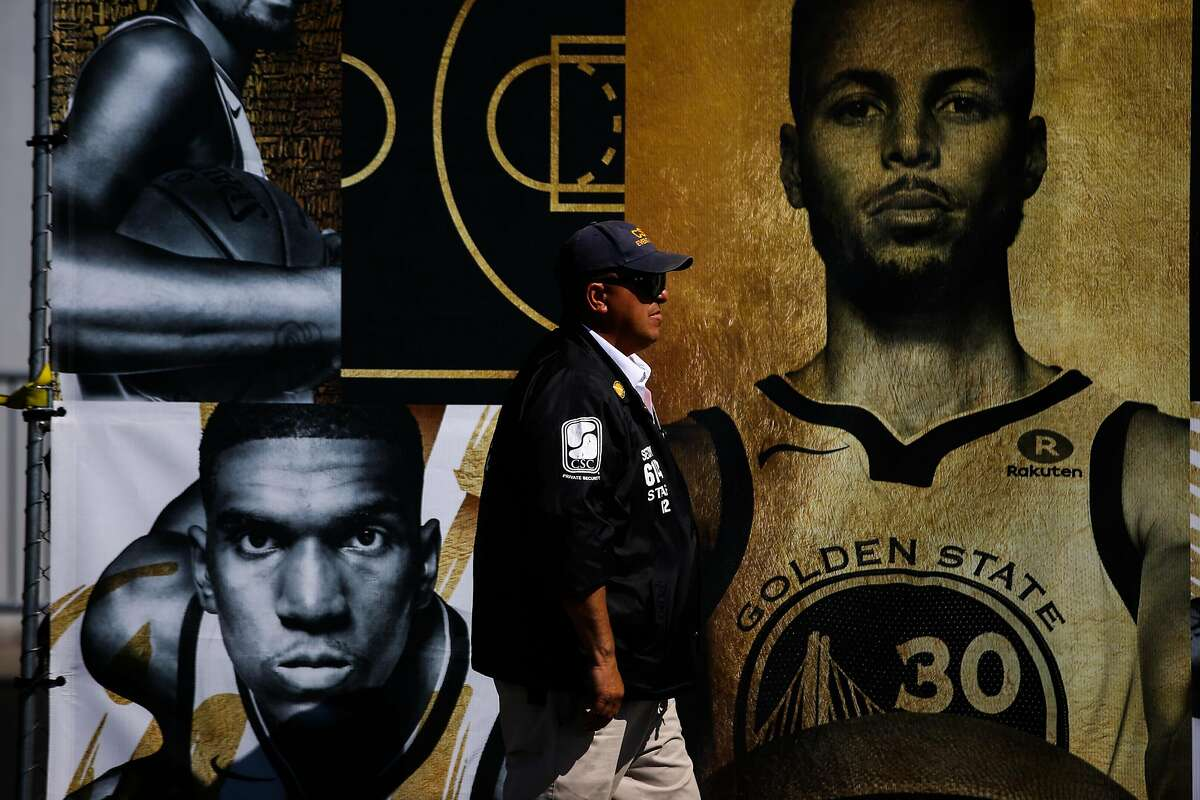 A security guard passes a banner outside Oracle Arena ahead of Game 2 of The NBA Finals between the Golden State Warriors and the Cleveland Cavaliers in Oakland, California, on Sunday, June 3, 2018.