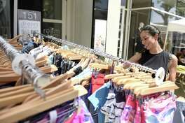 Greenwich's Daisy McRandal shops sale items at Lululemon at the 2018 Sidewalk Sale Days in downtown Greenwich, Conn. Thursday, July 12, 2018. Presented by the Greenwich Chamber of Commerce, more than 110 merchants marked down clothing, jewelry and accessories, attracting thousands of shoppers from near and far. The sidewalk sale continues Friday, Saturday and Sunday.