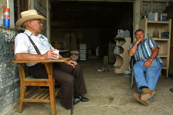 Elmor Buth (L) chats with Crawford Feed & Grain owner Kenneth Dieterich (R) about life as they have each Saturday for the past 10 years, in Crawford, Texas, 23 June 2001. US President George W. Bush will be hosting Russian President Vladimir Putin at his ranch-style home in the countryside in his hometown of Crawford (pop. 631) this summer or fall with a full scale summit, including hundreds of news reporters and White House staff.
