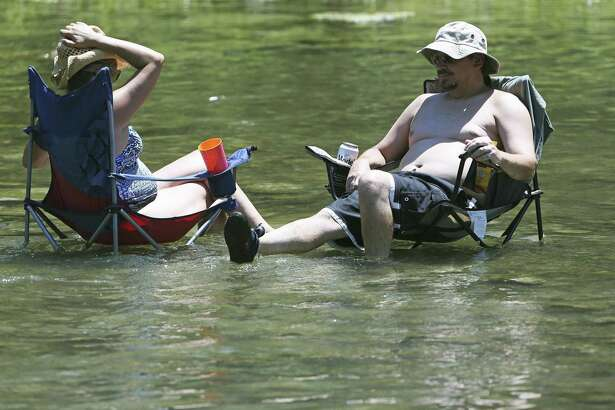 A couple takes to the Guadalupe River to cool off as 100-degree temperatures overtake the New Braunfels area Thursday.