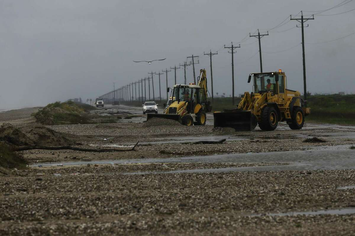 Crews work to clear sand and debris from Texas 87 after Tropical Storm Cindy made landfall on June 22, 2017 on the Bolivar Peninsula.