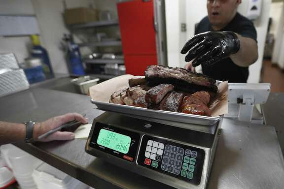 Russell Roegels of Roegels Barbecue Company, weighs meat on a scale behind the cash register, after Gudiel Tumax cuts it June 30 in Houston. Agriculture Commissioner Sid Miller has waged a war on BBQ joints, fining them for failing to follow rules the attorney general has said won't hold up in court.