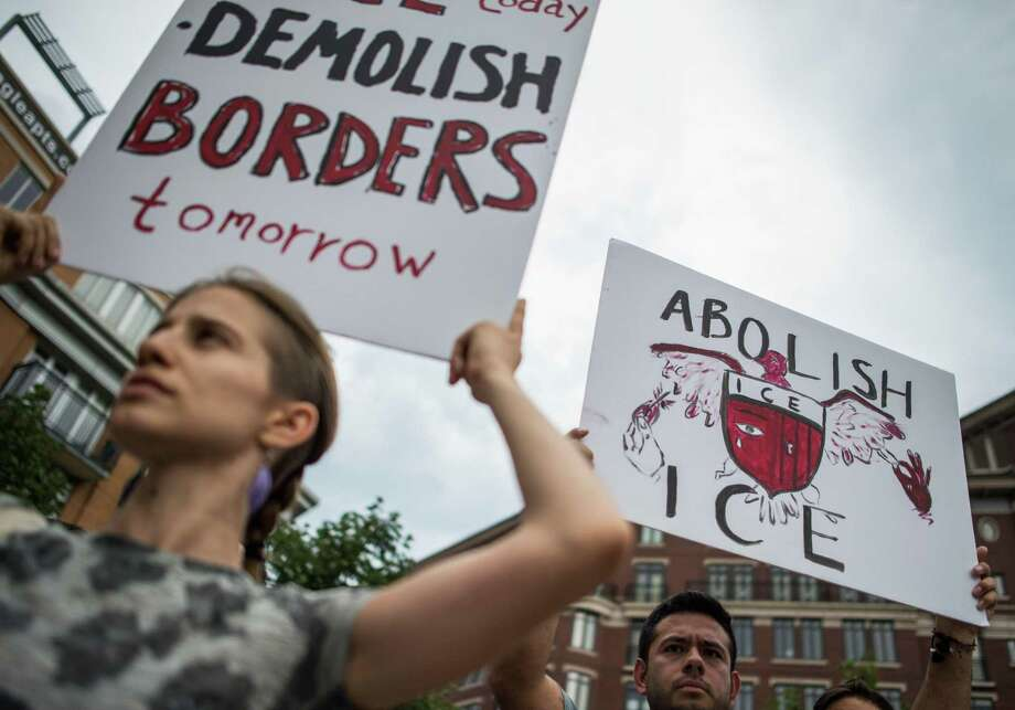 People hold up signs as they protest the U.S. Immigration and Customs Enforcement agency (ICE) and the recent detentions of illegal immigrants in Washington, D.C. on July 16. The coalition of activists called on the government to abolish ICE, a good slogan but a bad idea. Photo: ANDREW CABALLERO-REYNOLDS /AFP /Getty Images / AFP or licensors