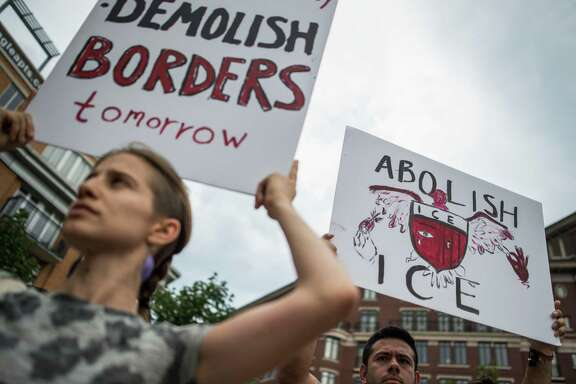 People hold up signs as they protest the U.S. Immigration and Customs Enforcement agency (ICE) and the recent detentions of illegal immigrants in Washington, D.C. on July 16. The coalition of activists called on the government to abolish ICE, a good slogan but a bad idea.