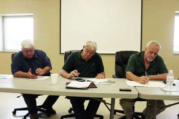Liberty County commissioners with heads buried into their cell phones do some quick math to determine the shared cost for the new invoice handed them by Harris County CTS.