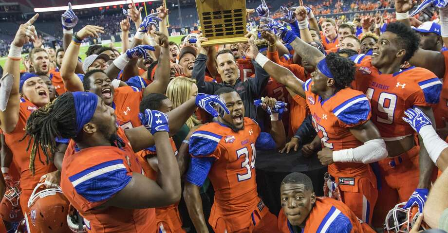 Sam Houston State head coach K.C. Keeler holds up the Battle of the Piney Woods trophy after defeating Stephen F. Austin 63-28 in a NCAA Football Championship Subdivision football game at NRG Stadium on Saturday, October 1, 2016, in Houston. (Joe Buvid / For the Houston Chronicle) Photo: Joe Buvid/For The Houston Chronicle