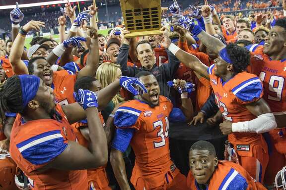 Sam Houston State head coach K.C. Keeler holds up the Battle of the Piney Woods trophy after defeating Stephen F. Austin 63-28 in a NCAA Football Championship Subdivision football game at NRG Stadium on Saturday, October 1, 2016, in Houston. (Joe Buvid / For the Houston Chronicle)
