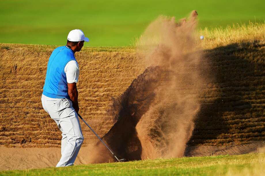 Tiger Woods blasts out of a bunker on the 14th hole at Carnoustie Golf Club on his way to a 71. Photo: Stuart Franklin / Getty Images