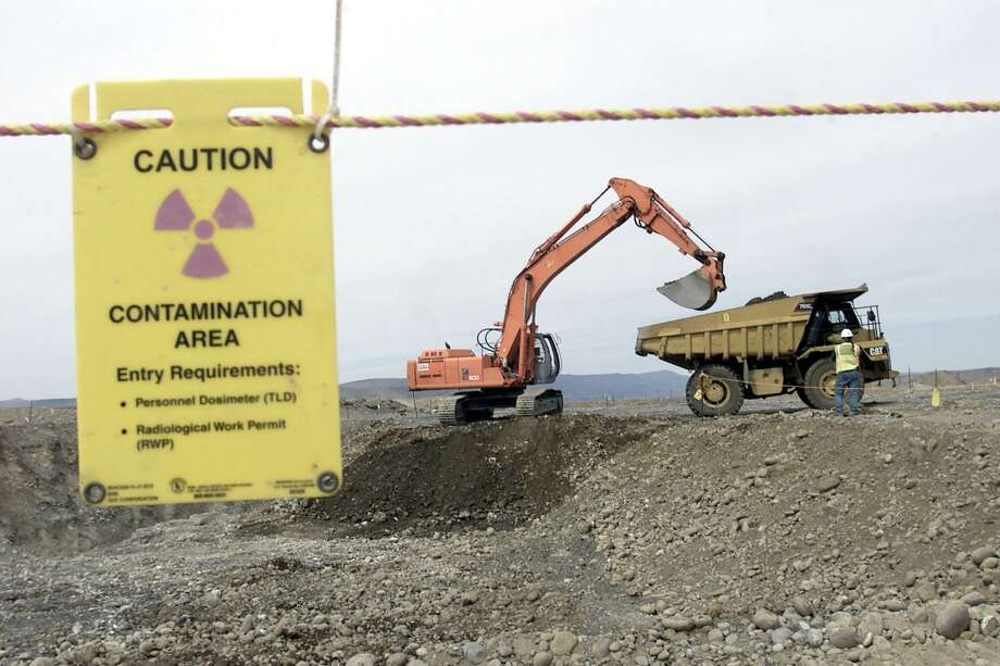 FILE-  This May 6, 2004 file photo shows workers as they remove waste in an area near two dormant nuclear reactors on the Hanford nuclear reservation, near Richland, Wash.  The world's first full-scale nuclear reactor is one stop on tours of the southeastern Washington state reservation created as part of the Manhattan Project to build the atomic bomb. Now, more than two decades after it stopped producing plutonium, Hanford is the nation's most contaminated nuclear site.  (AP Photo/Jackie Johnston, FILE) Photo: JACKIE JOHNSTON, STR / AP / AP2004