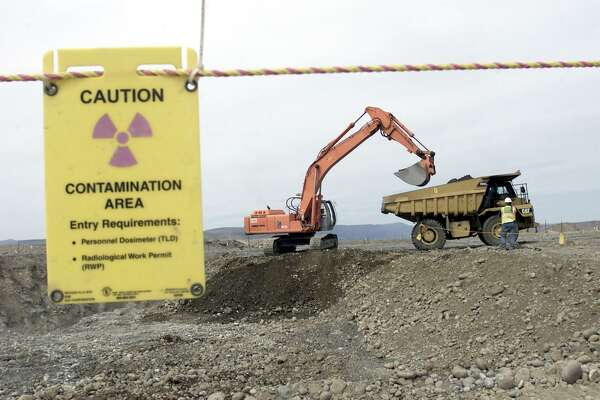 FILE- This May 6, 2004 file photo shows workers as they remove waste in an area near two dormant nuclear reactors on the Hanford nuclear reservation, near Richland, Wash. The world's first full-scale nuclear reactor is one stop on tours of the southeastern Washington state reservation created as part of the Manhattan Project to build the atomic bomb. Now, more than two decades after it stopped producing plutonium, Hanford is the nation's most contaminated nuclear site. (AP Photo/Jackie Johnston, FILE)