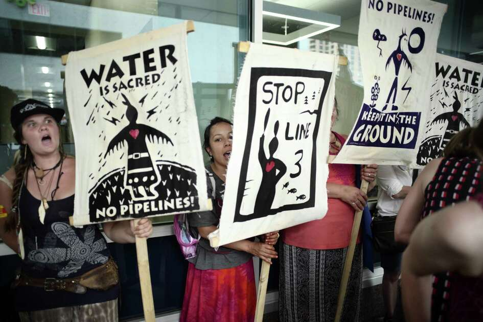 Activists protest the Line 3 decision, Thursday, June 28, 2018, in St. Paul, Minn. Minnesota regulators approved Enbridge Energy's proposal to replace its aging Line 3 oil pipeline, angering opponents who say the project threatens pristine areas and have vowed Standing Rock-style protests, if needed to block it. (Richard Tsong-Taatarii/Star Tribune via AP)