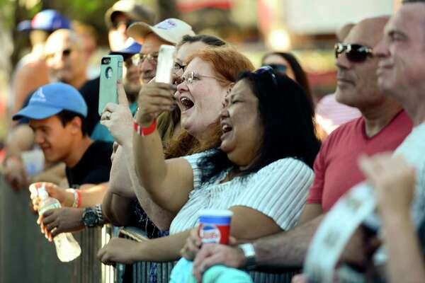 Concert fans snap photos of bands performing during the Alive@Five concert series in Columbus Park on July 19, 2018 in Stamford, Connecticut.