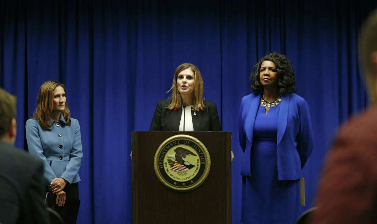 U.S. Attorney Erin Nealy Cox, center, holds a news conference on Friday, July 13, 2018 in Dallas. Federal prosecutors say eight MS-13 members have been indicted in Texas on charges tied to alleged gang activities including racketeering conspiracy, attempted murder and assault. Cox announced the charges. Officials describe the gang as one of the most ruthless and violent on the streets. (Vernon Bryant/The Dallas Morning News via AP)