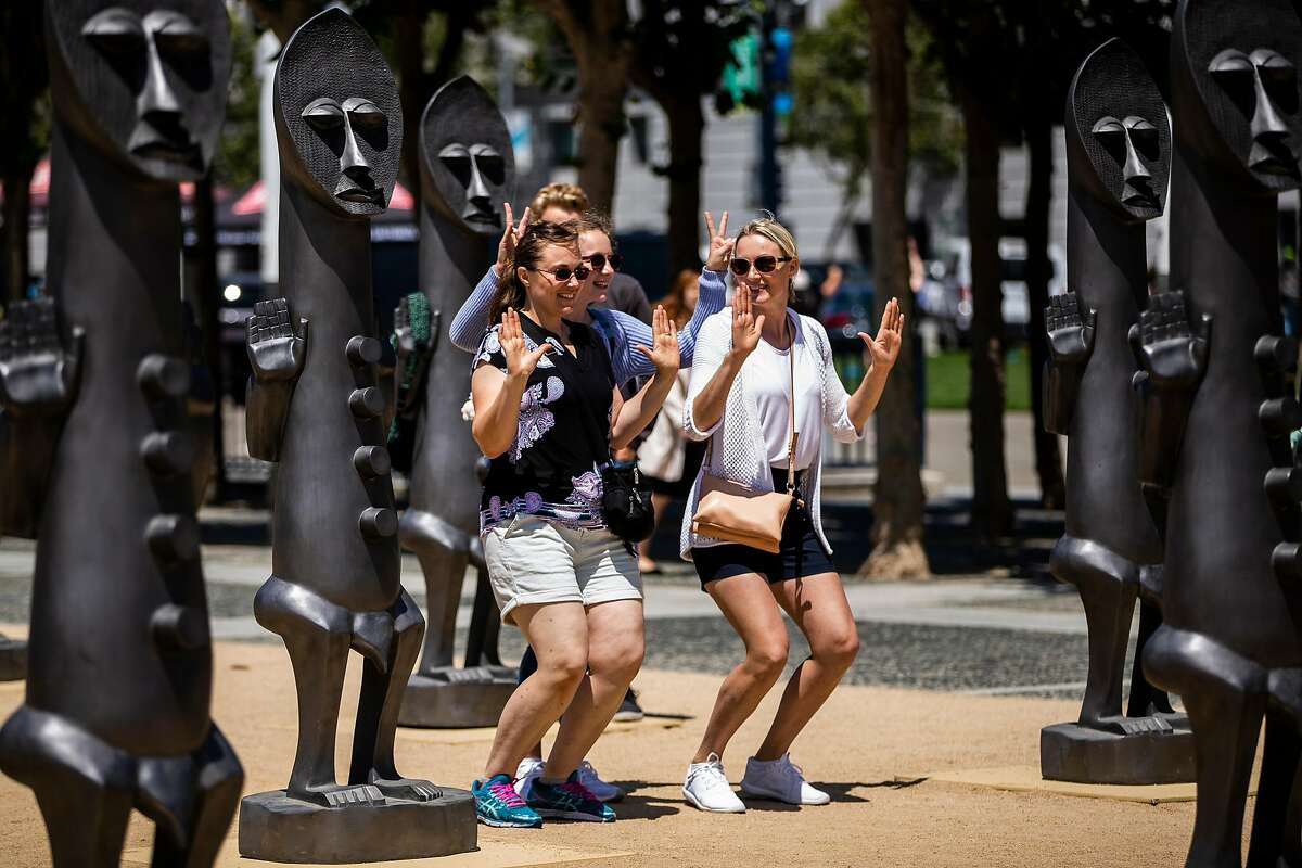 Members of the Valencia family, of Germany, gesture as they pose for a photo in front of The Invisible Man and the Masque of Blackness sculpture installation by Zak Ov� at Civic Center Plaza in San Francisco, Calif. on Thursday, July 19, 2018.