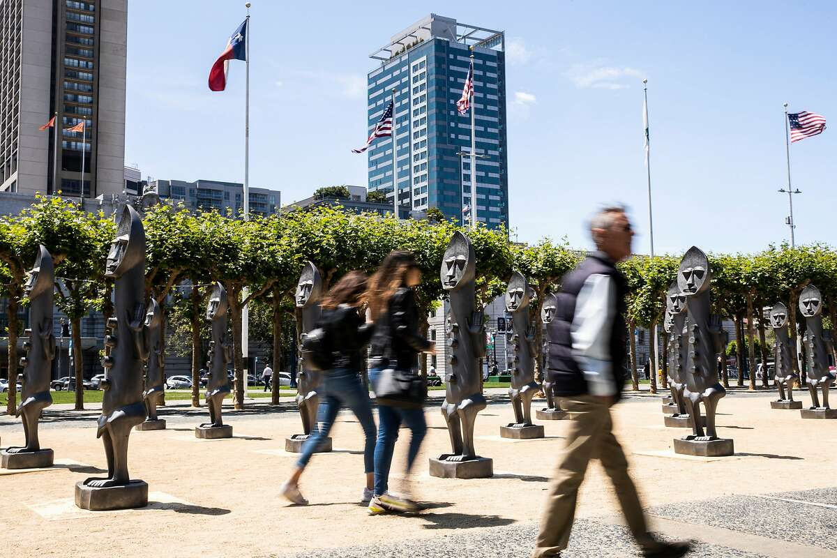 Pedestrians walk past The Invisible Man and the Masque of Blackness sculpture installation by Zak Ov� at Civic Center Plaza in San Francisco, Calif. on Thursday, July 19, 2018.
