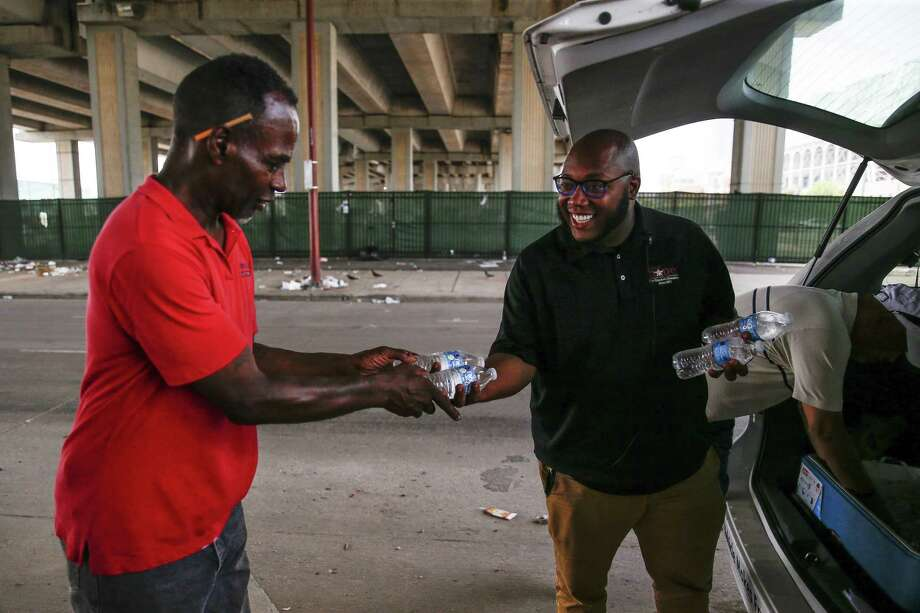 Star of Hope outreach case manager Kenneth DeVon, right, hands out cold water to a homeless man living under Highway 59 ahead of a heatwave that is expected to reach into the low 100s July 19, 2018 in Houston.