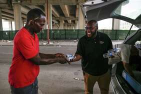 Star of Hope outreach case manager Kenneth DeVon, right, hands out cold water to a homeless man living under Highway 59 ahead of a heatwave that is expected to reach into the low 100s July 19, 2018 in Houston.        Continue clicking to see how Houstonians have beaten the heat over the decades.