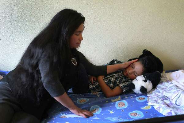 EL PASO, TX - JULY 19:  A woman, identified only as Delaria, sits with her sleeping son Alfredo, 9, in an Annunciation House facility after they were reunited earlier today on July 19, 2018 in El Paso, Texas.  The two, originally from Guatemala,  were reunited in an I.C.E processing center after being separated for three months when the two crossed into the United States. A court-ordered July 26th deadline is approaching for the U.S. government to reunite as many as 2,551 migrant children ages 5 to 17 that had been separated from their families.  (Photo by Joe Raedle/Getty Images)