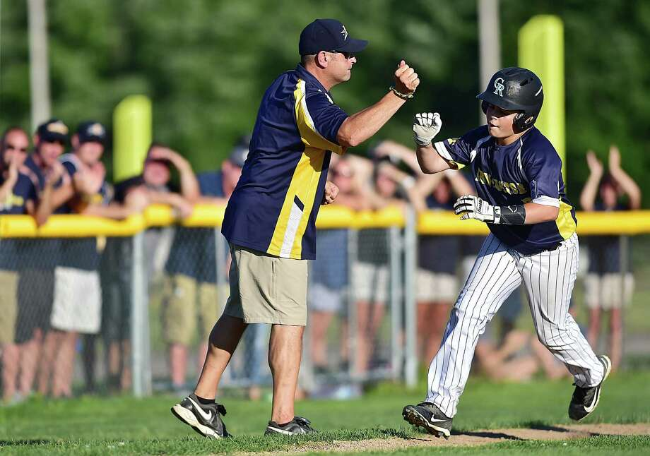 Newington's Nico Tolisano is congratulated by coach Tom Tolisano on his home run against Madison in a Section 3 Little League game Thursday in Rocky Hill. Photo: Catherine Avalone / Hearst Connecticut Media / New Haven Register