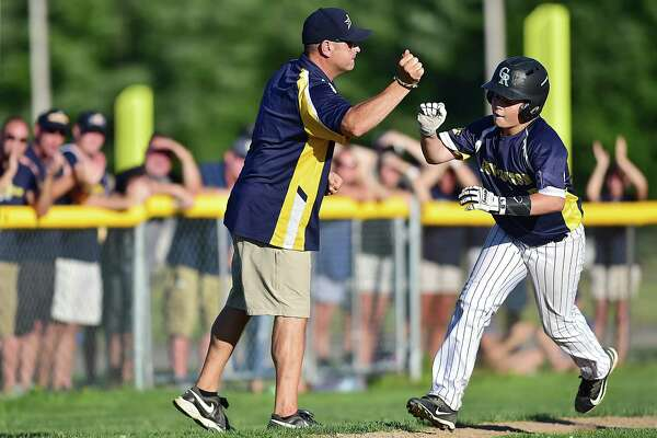 Newington's Nico Tolisano is congratulated by coach Tom Tolisano on his home run against Madison in a Section 3 Little League game Thursday in Rocky Hill.