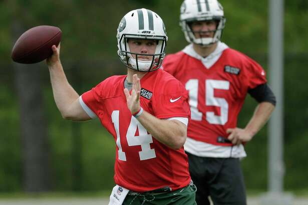 FILE - In this May 22, 2018, file photo, New York Jets quarterback Josh McCown, right, watches as quarterback Sam Darnold throws during practice at the NFL football team's training camp in Florham Park, N.J. Darnold and Josh Allen are spending their weekend watching greatness, and for once it's not other football players. They're at Shinnecock Hills for the U.S. Open golf tournament. (AP Photo/Seth Wenig, File)