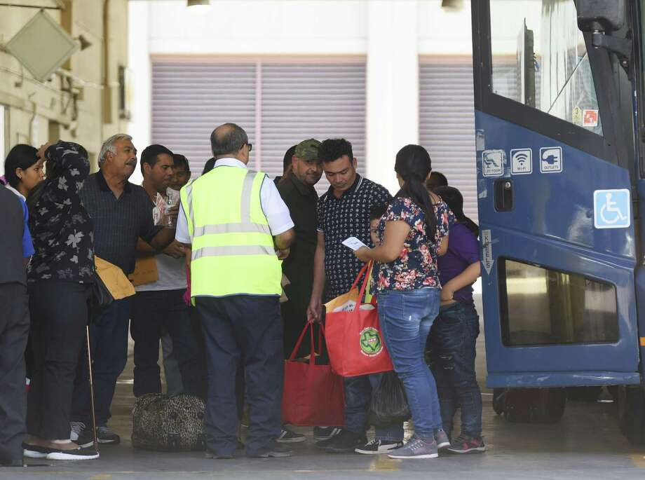 Immigrant families arrive at the San Antonio Greyhound bus station Thursday. Many will go on to other cities. Photo: Billy Calzada /Staff Photographer / Billy Calzada