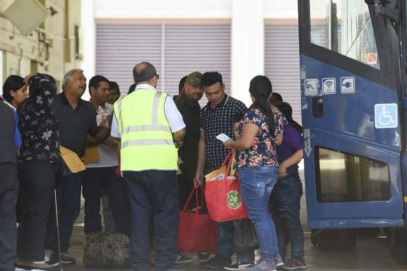 Immigrant families arrive at the San Antonio Greyhound bus station Thursday. Many will go on to other cities.