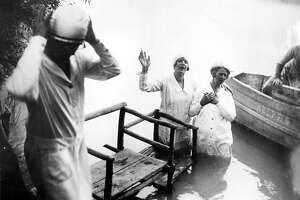 Aimee McPherson, center, about to baptize one of her followers in the River Jordan in Palestine, May 8, 1930.
