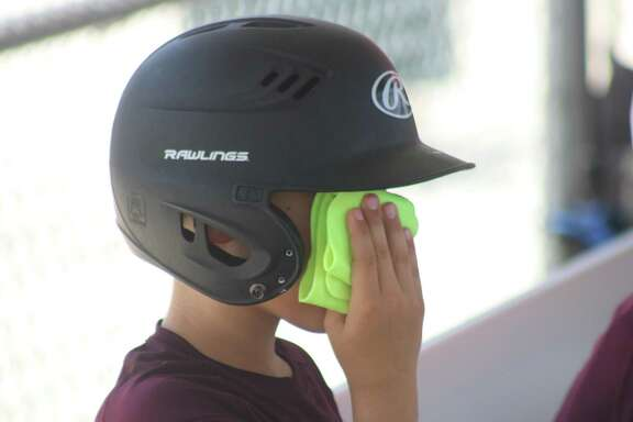 Aiden Gorom applies a cold piece of cloth to his face as he and his teammates sought ways to keep the summer temperatures at arm's length during Thursday's second South Zone  game.