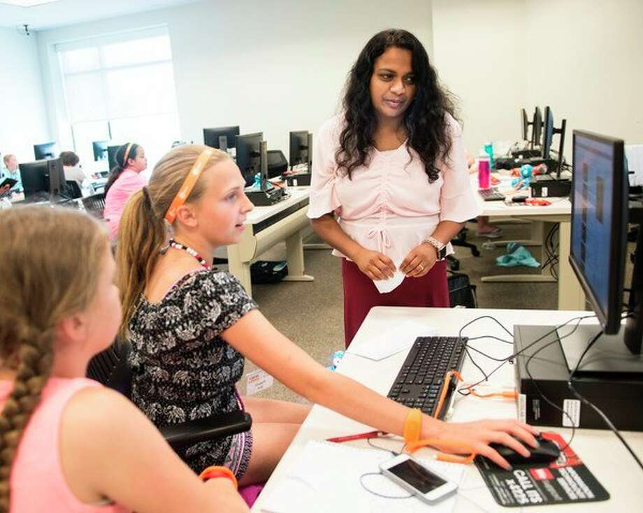 Rajani Muraleedharan, right, SVSU associate professor of electrical and computer engineering, works with middle school students to encourage their interest in math and science during an earlier Camp Infinity session at SVSU on June 28. (Photo provided/Tim Inman, SVSU)