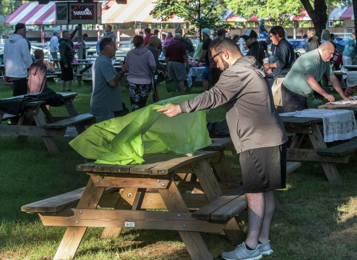 Greg Smethhurst of Cohoes lays a table cloth carefully on a picnic table which he will use on Opening day at the Saratoga Race Course Friday July 20, 2018 in Saratoga Springs, N.Y. (Skip Dickstein/Times Union)