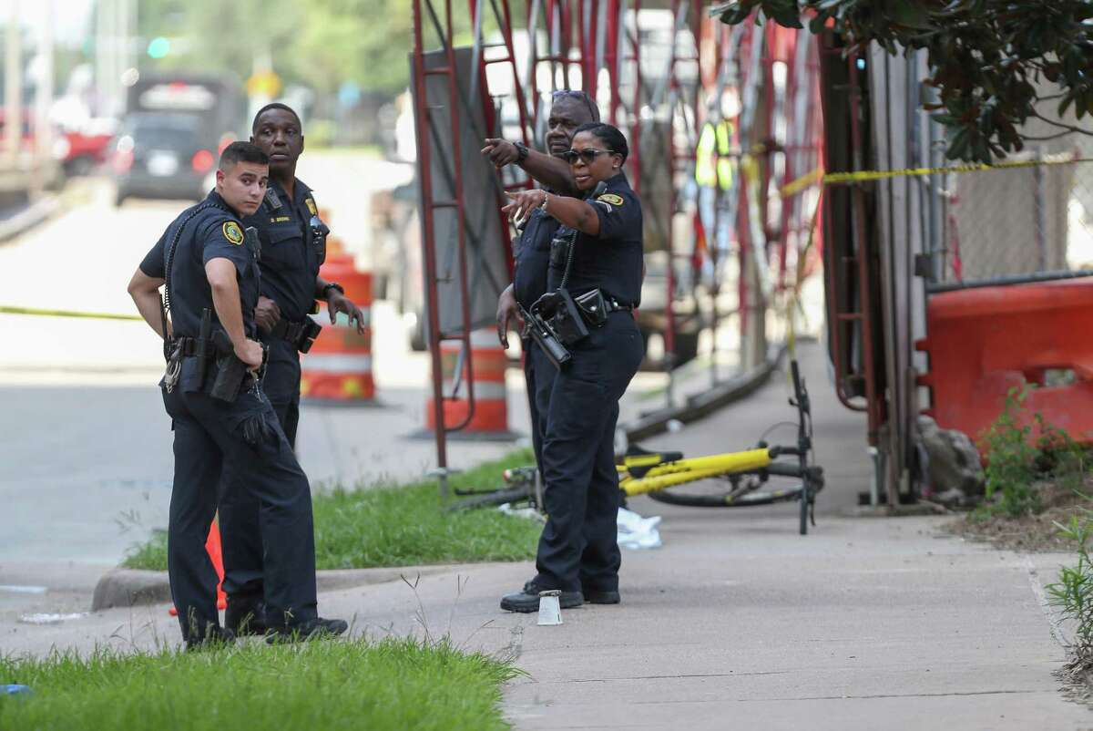 Houston police officers investigate the scene of a homicide near Holcombe and Main Friday, July 20, 2018, in Houston. Cardiologist Dr. Mark Hausknecht, was shot and killed while riding a bicycle.