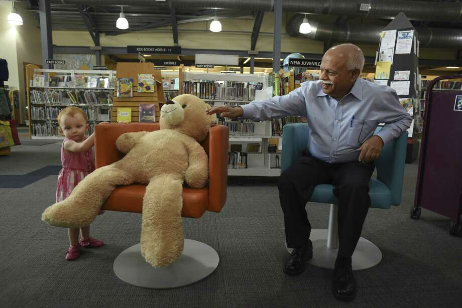 Sam Mammen, who recently donated $2 million to the newly renamed Mammen Family Public Library in Bulverde, vies for the attention of Joni David, who was visiting the library with her mother. Photo: Billy Calzada /San Antonio Express-News / San Antonio Express-News