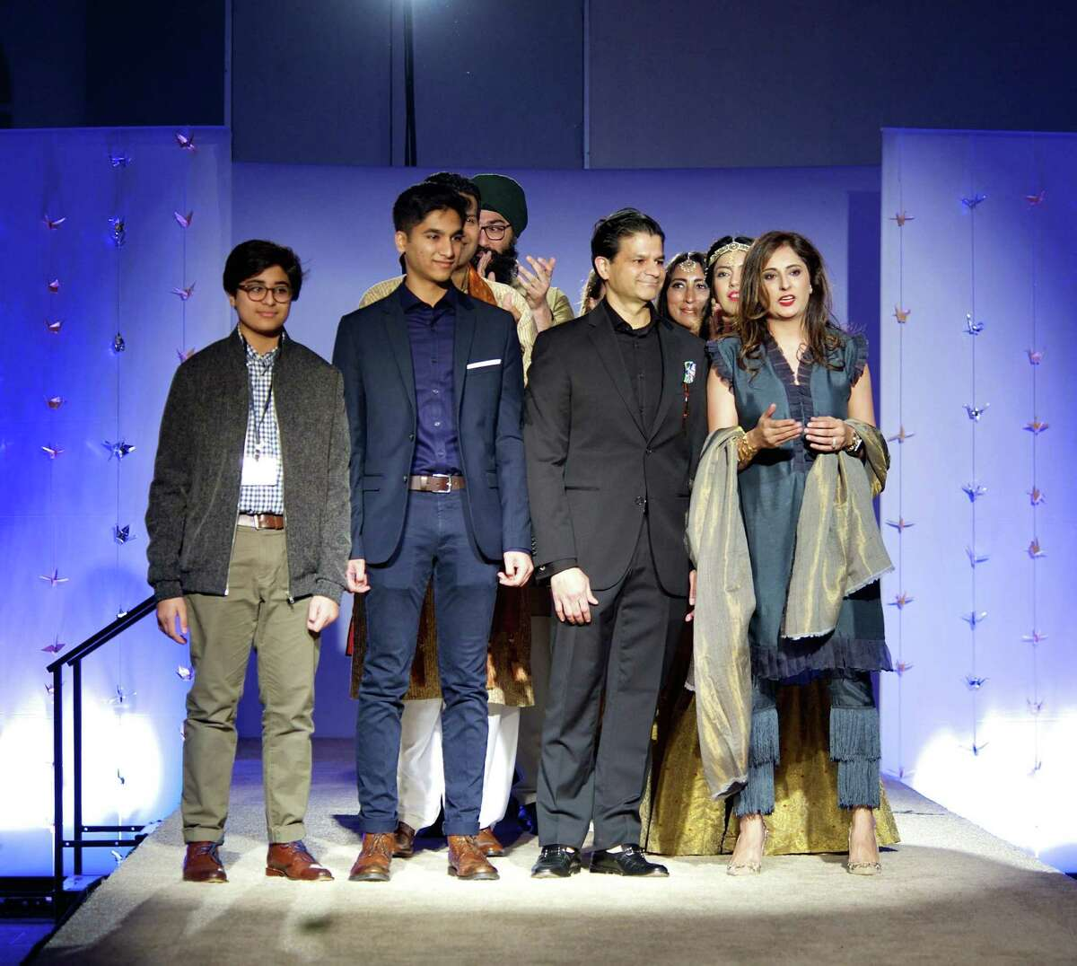 During the finale of her 2018 fashion show, Roshnic Latif stands with her family (from left) sons Hashim and Huzair and husband Wasif.