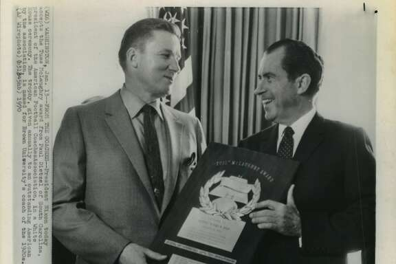 From the coaches - President Nixon today accepts the Tuss McLaughry award from Paul Dietzel of South Carolina, president of the American Football Coaches Association, in a White House ceremony.  The trophy, given annually to an outstanding American by the association, is named for Brown University's coach of the 1920s.