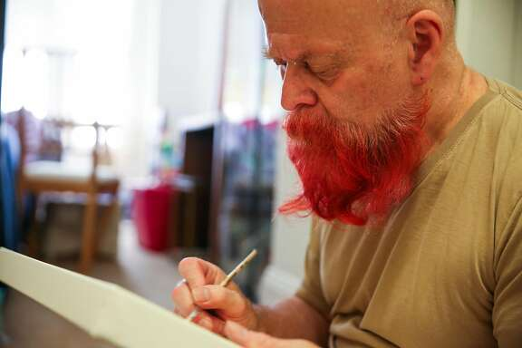 Tim Snyder works on a painting in his apartment in the Tenderloin in San Francisco, California, on Wednesday, July 18, 2018.