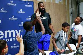 Rockets guard James Harden high fives Jatavion O'Connor, 11, after surprising 10 underprivileged kids from the Boys & Girls Club of Greater Houston with a $200 back to school shopping spree at Academy Sports and Outdoors July 20, 2018 in Houston.
