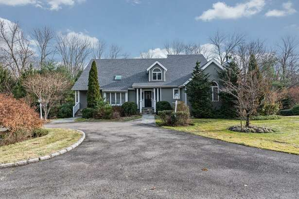 The gray contemporary colonial house at 2 Talmadge Hill Road is set on a two-acre property in a location convenient to the Talmadge Hill train station, Merritt Parkway, and the town centers of Darien and New Canaan.