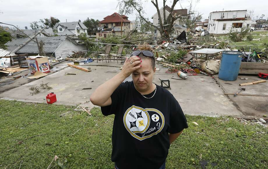 Crystal Jensen stands in front of what's left of her shattered home in Marshalltown, Iowa. Forecasting models early Thursday had showed only a slight chance of strong thunderstorms. Photo: Charlie Neibergall / Associated Press