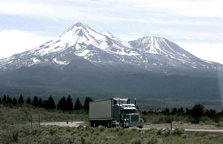 FILE -- In this June 19, 2008, file photo a truck drives past Mount Shasta near Weed, Calif. California and 14 other states are suing the Trump administration over its decision to suspend an Obama-era rule aimed at limiting pollution from trucks. The lawsuit filed Thursday, July 19, 2018, in the U.S. Court of Appeals for the District of Columbia Circuit says the July 6 decision by the Environmental Protection Agency was illegal and could put thousands of additional highly polluting trucks on the roads. (AP Photo/Rich Pedroncelli, File)