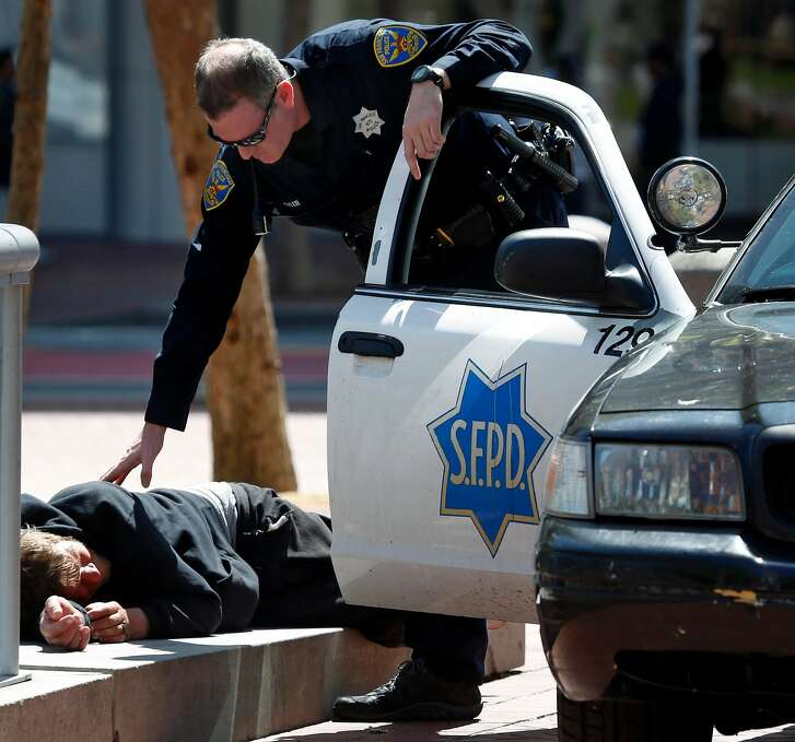 A police officer checks on the well being of a man lying down at United Nations Plaza in San Francisco, Calif. on Thursday, April 20, 2017. The city may soon become the first in the United States to open a safe injection site for intravenous drug users.