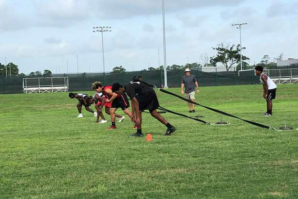 Members of the Crosby Cougar football team prepare to run while dragging weighted sleds behind them during the final day of summer EDGE workouts, July 19, at Crosby High School