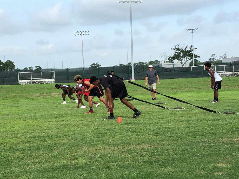 Members of the Crosby Cougar football team prepare to run dragging weighted sleds behind them during the final day of summer EDGE workouts, July 19, 2018 at Crosby High School Photo: Elliott Lapin