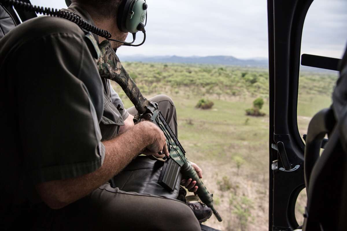FILE - A South African ranger searches from a helicopter for a poacher on the run in Kruger National Park, South Africa.
